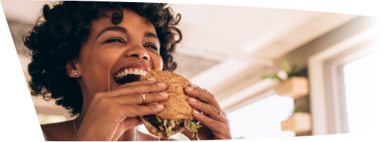 Woman smiling and eating a sandwich