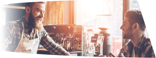 Bearded barista behind counter at coffee shop laughing with customer