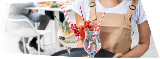 Aproned waitress serving a tray of cocktails with fruit garnishes and multiple striped straws