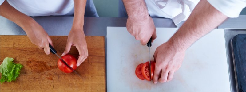 Chef chopping yellow peppers on wooden chopping board
