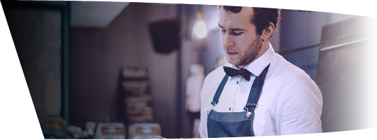 Waiter with bow tie and apron looking down